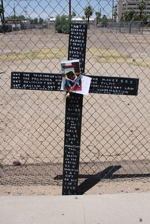 BLACK CROSS CHAINED TO FENCE